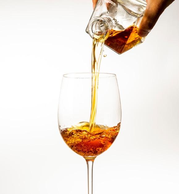 Le bevande alcoliche vengono versate in un bicchiere di decanter su uno sfondo chiaro Foto Premium
