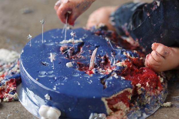 Le braccia del bambino di compleanno caucasico mentre distruggono e schianta la torta di glassa blu Foto Gratuite