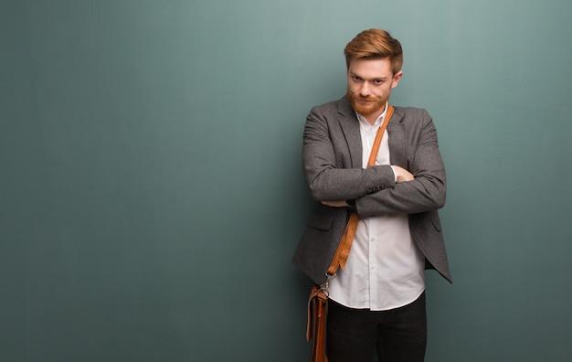 Le braccia dell'incrocio dell'uomo di affari della giovane testarossa si sono rilassate Foto Premium