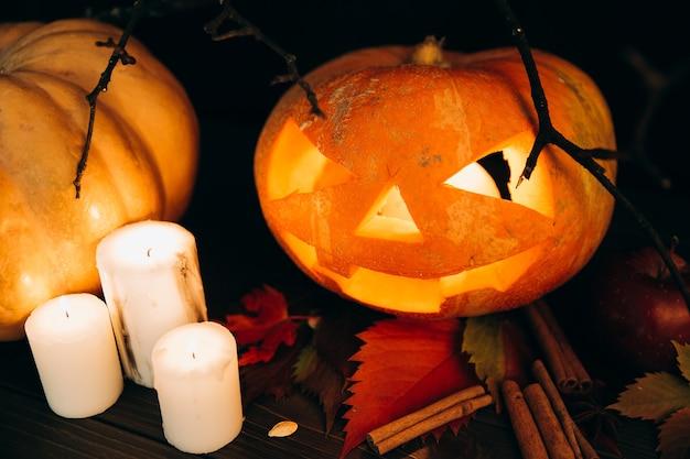 Le candele bianche stanno prima della zucca scarry di halloween su cannella Foto Gratuite