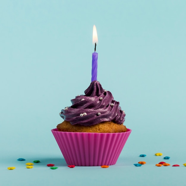 Le candele burning viola sui muffin decorativi con la stella variopinta spruzza contro il contesto blu Foto Gratuite