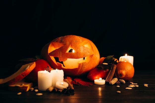 Le candele lucenti, la cannella e le foglie cadute stanno prima della zucca di halloween scarry Foto Gratuite