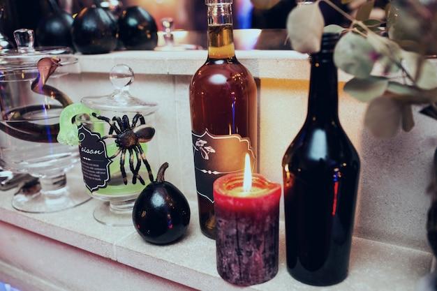 Le candele nere si stendono tra le bottiglie con vino Foto Gratuite