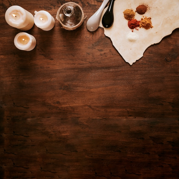 Le candele si avvicinano alla bottiglia e gli ingredienti su pergamena Foto Gratuite