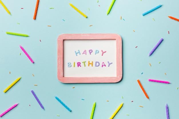 Le candele variopinte e spruzza sparse intorno alla struttura bianca di buon compleanno su fondo blu Foto Gratuite