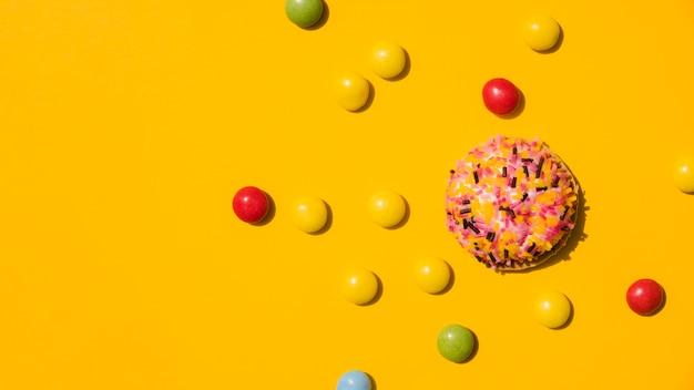 Le caramelle con spruzzano la ciambella su fondo giallo Foto Gratuite