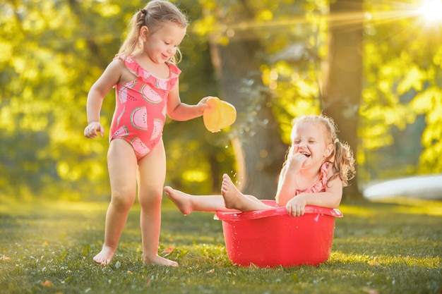 Le carine bambine bionde che giocano con l'acqua spruzza sul campo in estate Foto Gratuite