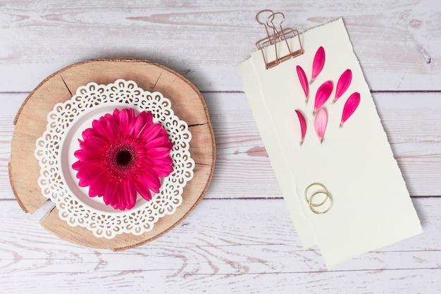 Le carte con i petali e gli anelli si avvicinano al fiore su legno rotondo Foto Gratuite