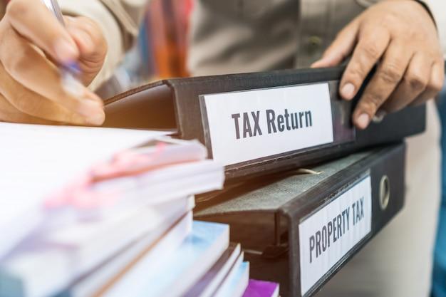 Le cartelle delle dichiarazioni dei redditi e delle imposte patrimoniali si impilano con il raccoglitore di etichette nero sul rapporto di riepilogo del documento cartaceo Foto Premium