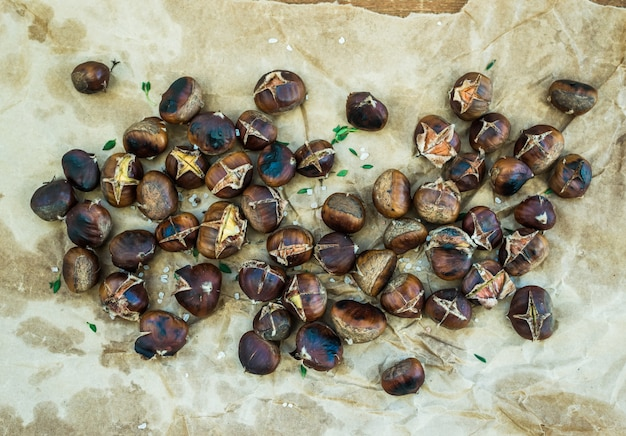 Le castagne arrostite sul mestiere consumato oleoso incartano la tavola di legno rustica, vista superiore. Foto Premium