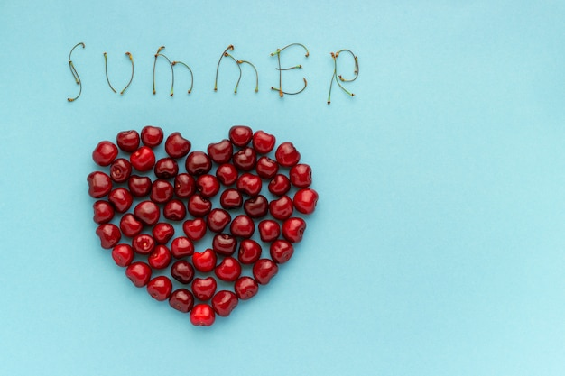 Le ciliege della bacca rossa modellano il cuore ed il testo estate su fondo blu copi lo spazio Foto Premium