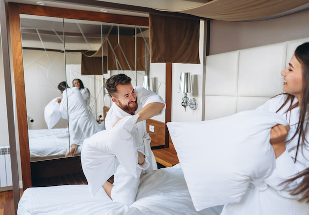 Le coppie allegre si divertono nella lotta della camera da letto con i grandi cuscini a casa Foto Gratuite