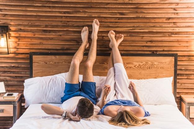 Le coppie che si tengono mano che si trova sul letto Foto Gratuite