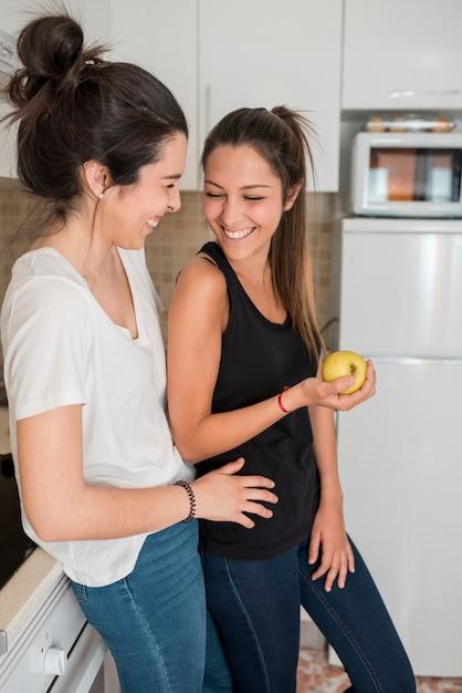 Le coppie delle giovani donne di risata che stanno nella cucina Foto Gratuite