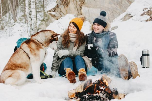 Le coppie felici con il cane haski al parco naturale della foresta nella stagione fredda Foto Premium
