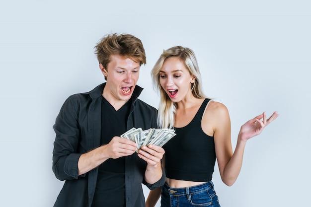 Le coppie felici mostrano la banconota del dollaro fanno un certo affare Foto Gratuite