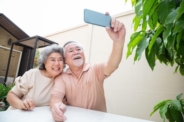 Le coppie senior asiatiche che parlano nella video chiamata chiacchierano sul telefono cellulare o che prendono un selfie, la tecnologia astuta per la vecchiaia e l'attivismo online che rimangono il concetto collegato Foto Premium