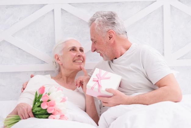 Le coppie senior romantiche che se lo esaminano che tengono il mazzo ed il contenitore di regalo dentro hanno avuto Foto Gratuite