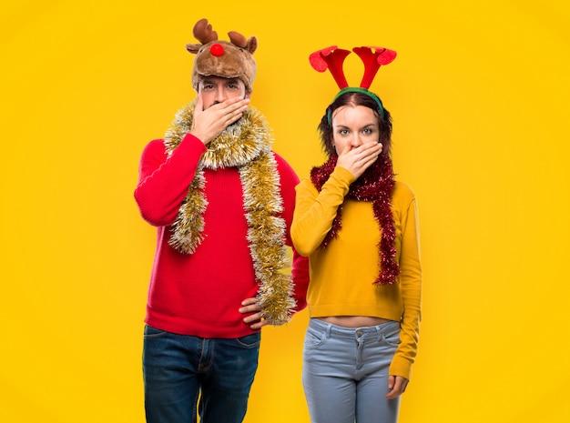 Le coppie si sono agghindate per le feste di natale che coprono la bocca di mani per dire qualcosa Foto Premium