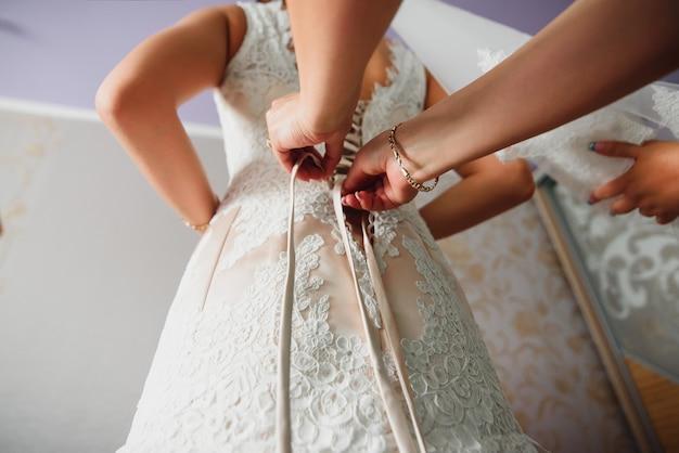 Le damigelle aiutano a raccogliere la damigella e allacciare il vestito Foto Premium