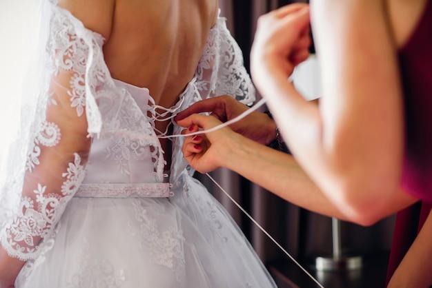Le damigelle allacciano l'abito bianco da sposa sulla schiena della sposa il giorno del matrimonio Foto Premium