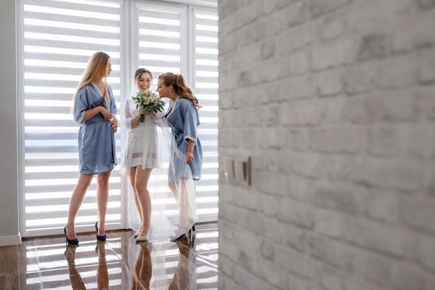 Le damigelle con la sposa vestita con indumenti da notte setosi odorano il profumo del bouquet da sposa Foto Gratuite