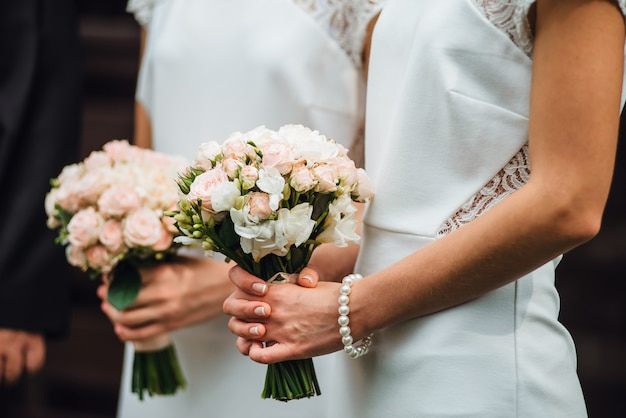 Le damigelle in abiti bianchi reggono mazzi di rose Foto Premium