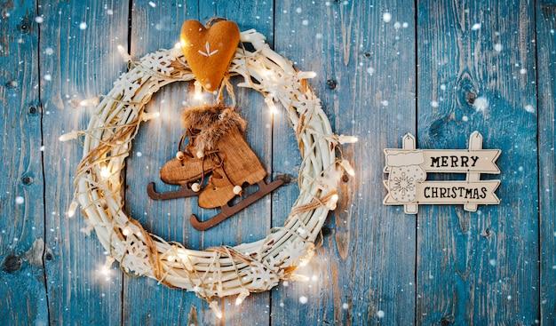 Le decorazioni del nuovo anno intorno al natale segnano lo spazio vuoto con lettere per le ghirlande delle luci brucianti del testo su fondo di legno blu. Foto Premium