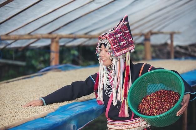Le donne akha sorridevano e portavano un cesto di caffè in grani Foto Gratuite