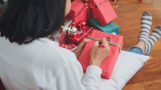 Le donne asiatiche celebrano il festival di natale. il maglione teenager femminile di usura e il cappello di santa si rilassano felici scrivono un desiderio sul regalo vicino all'albero di natale godono insieme delle vacanze invernali di natale in salone a casa. Foto Gratuite
