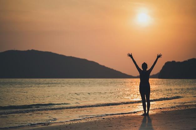 Le donne asiatiche giocano a yoga su una spiaggia di sabbia sul mare e in montagna la mattina all'alba. concetto di esercizio e meditazione. Foto Premium