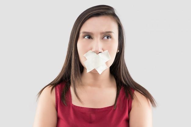 Le donne asiatiche in abiti rossi usano del nastro adesivo per chiudere la bocca Foto Premium