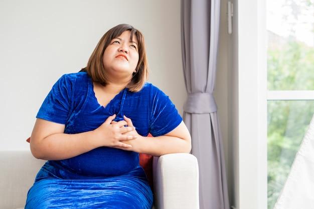 Le donne asiatiche in sovrappeso sono sedute sul divano del soggiorno. e maniglie al petto a causa di malattie cardiache Foto Premium