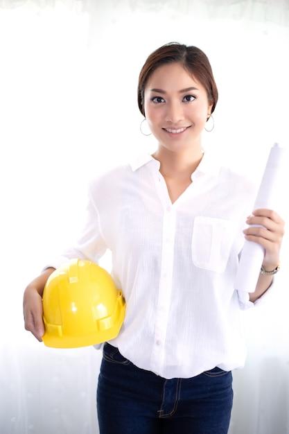Le donne asiatiche ingegnere ispezionando e lavorando e tenendo i modelli in ufficio Foto Premium