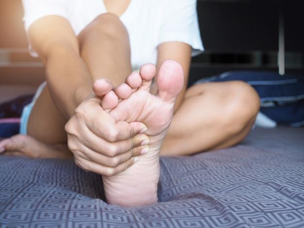 Le donne asiatiche usano le mani per massaggiare la pianta dei piedi e il dolore al tallone, lesioni del dolore al piede. Foto Premium