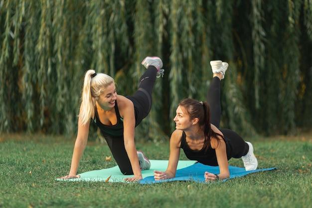 Le donne atletiche che fanno l'yoga si esercita fuori Foto Gratuite
