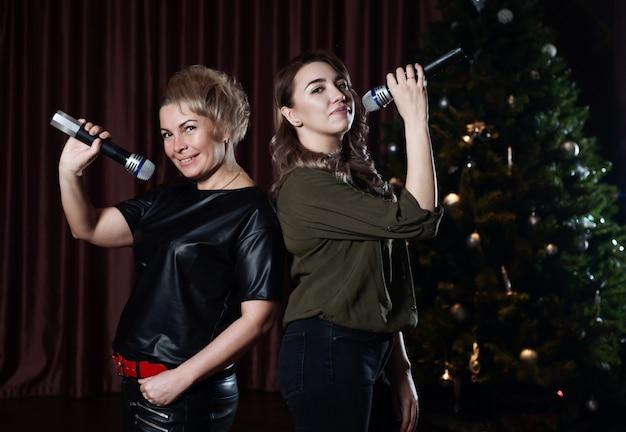 Le donne cantano sul palco in microfoni in karaoke contro l'albero di natale Foto Premium