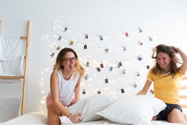 Le donne che giocano i cuscini combattono insieme sul letto Foto Premium