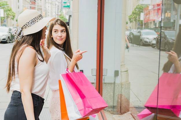 Le donne con i sacchetti della spesa variopinti si avvicinano alla finestra del negozio Foto Gratuite