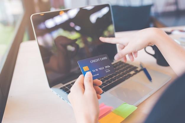 Le donne d'affari usano carte di credito e computer portatili per fare acquisti online. Foto Premium