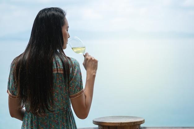 Le donne del primo piano bevono il vino bianco con un bicchiere di vino sulla terrazza vista mare Foto Premium