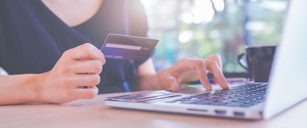 Le donne di affari usano a mano le carte di credito ed i computer portatili per acquistare online. Foto Premium