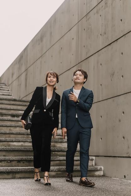 Le donne e gli uomini asiatici di affari stanno camminando e parlando insieme Foto Premium
