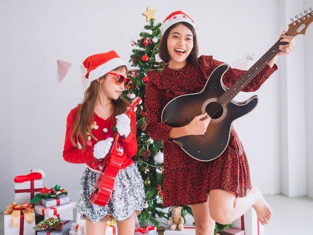 Le donne e i bambini asiatici festeggiano il natale strimpellando la chitarra in casa Foto Premium
