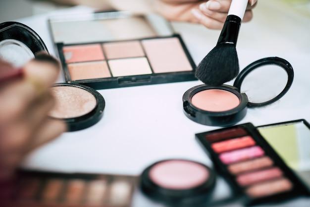 Le donne facendo il trucco con pennello e cosmetici Foto Gratuite