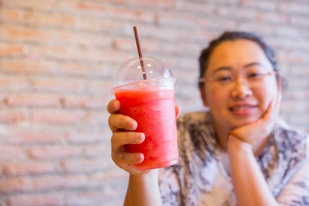 Le donne grasse tubby bere frutta frullato frutta bevanda sana buona per dieta e ghiaccio fresco per una giornata calda Foto Premium
