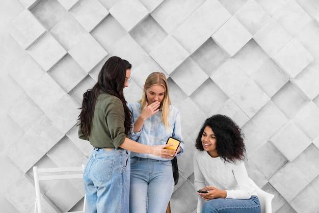 Le donne in ufficio guardando sul cellulare Foto Gratuite