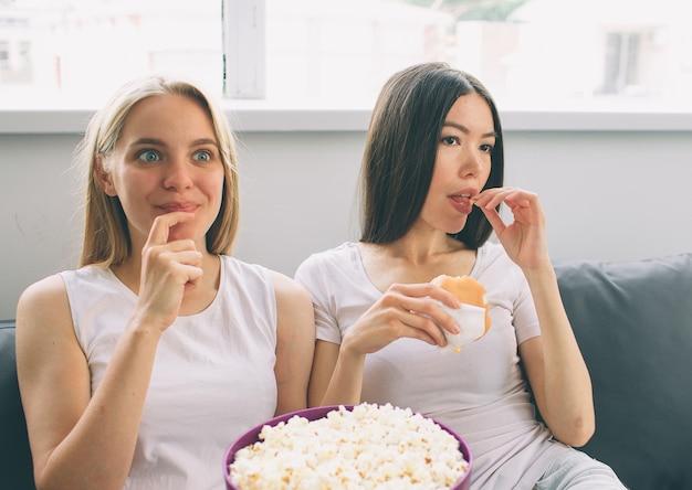 Le donne mangiano popcorn e hamburger e guardano la tv Foto Premium