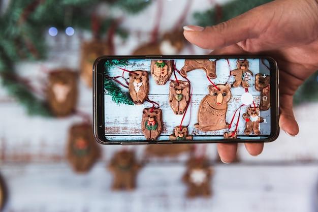 Le donne prendono foto sul telefono biscotti fatti in casa della famiglia dell'orso di panpepato di natale con glassa di zucchero su un bellissimo legno. disteso Foto Premium