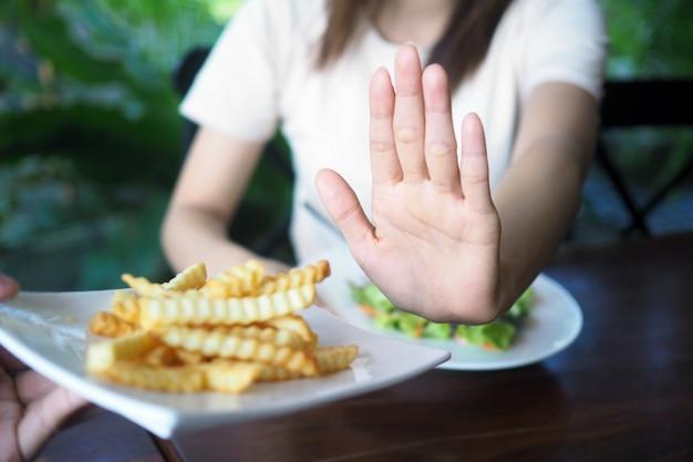 Le donne si rifiutano di mangiare fritti o patatine fritte per perdita di peso e buona salute. Foto Premium